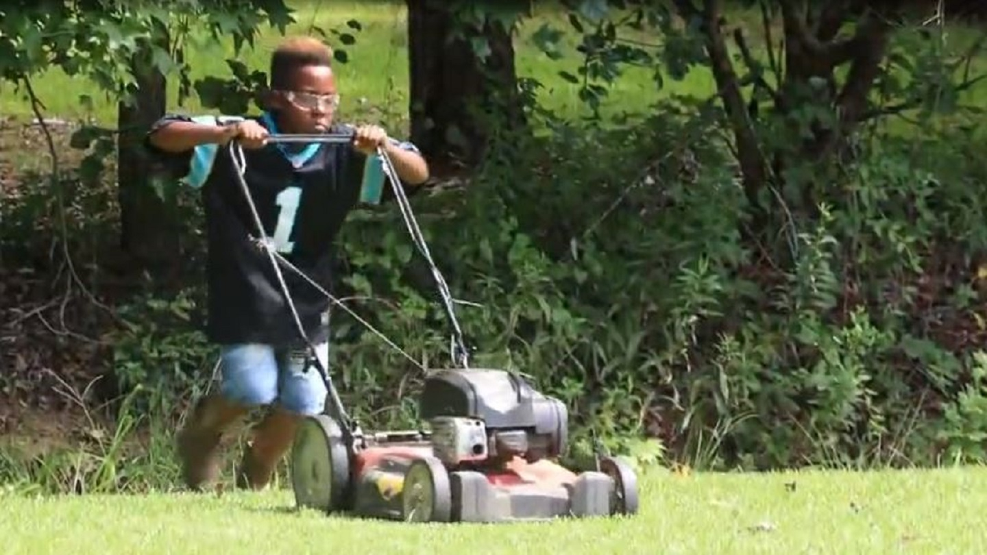 12-year-old boy is cutting grass so he can pay for college